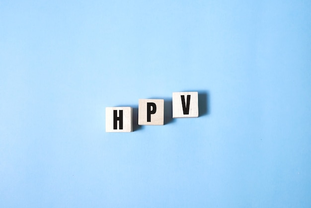 Hpv word written on wood block. hpv text on blue for your desing, top view concept.