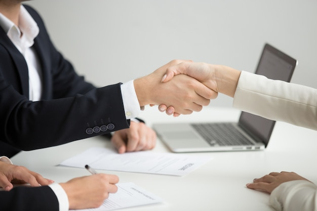 Hr handshaking successful candidate getting hired at new job, closeup Free Photo