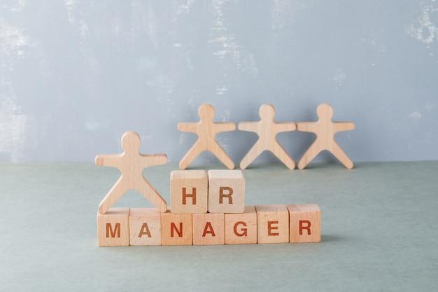 Концепция менеджера hr с деревянными блоками со словами на нем, деревянными человеческими фигурами. Бесплатные Фотографии