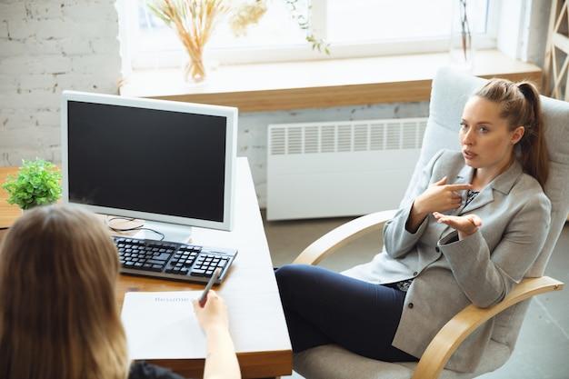Молодая женщина сидит в офисе во время собеседования с работницей, начальником или hr-менеджером, разговаривает, думает, выглядит уверенно Бесплатные Фотографии