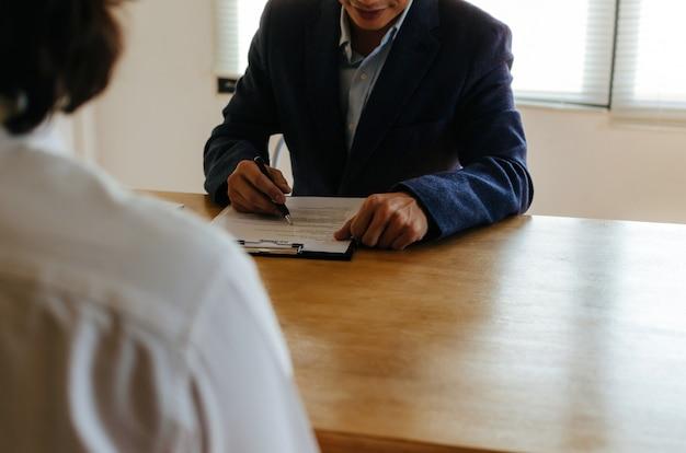 Бизнес hr менеджер чтения резюме с молодым человеком во время собеседования и объяснения о его профиле, сидя в конференц-зале в офисе, людских ресурсов, бизнес собеседование, концепция занятости Premium Фотографии