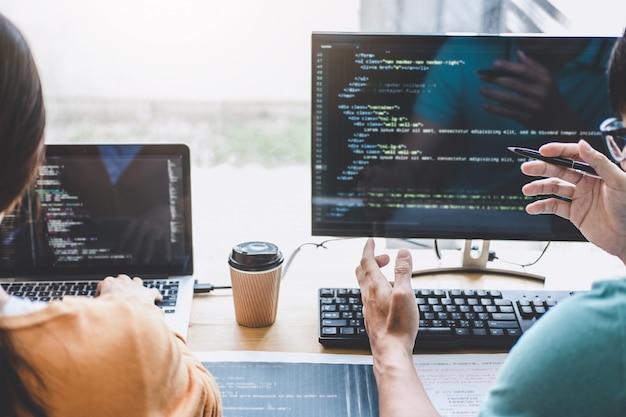 コードを書くこととデータコード技術をタイプすること、プログラマーは会社のデスクトップコンピュータで開発しているソフトウェアでウェブサイトプロジェクトに取り組んでいる協力、html、phpとjavascriptによるプログラミング Premium写真