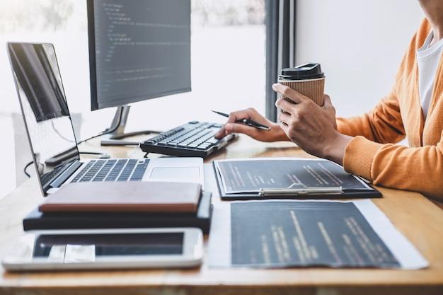 プログラミングの開発に携わっている若いプロフェッショナルプログラマー、ソフトウェアの開発会社の事務所、コードの作成およびデータコードの入力、html、php、およびjavascriptによるプログラミング Premium写真