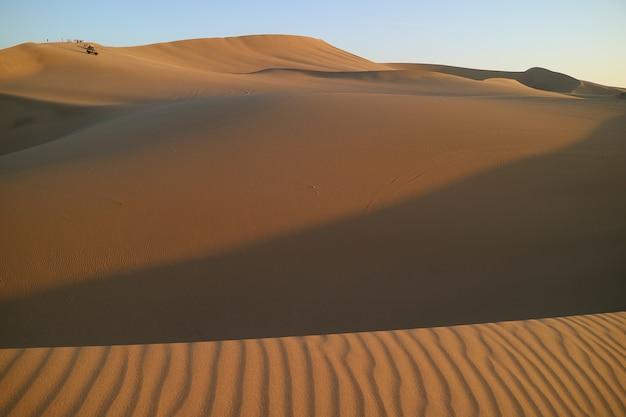 Huacachinaの広大な砂丘で夕日を待っています Premium写真