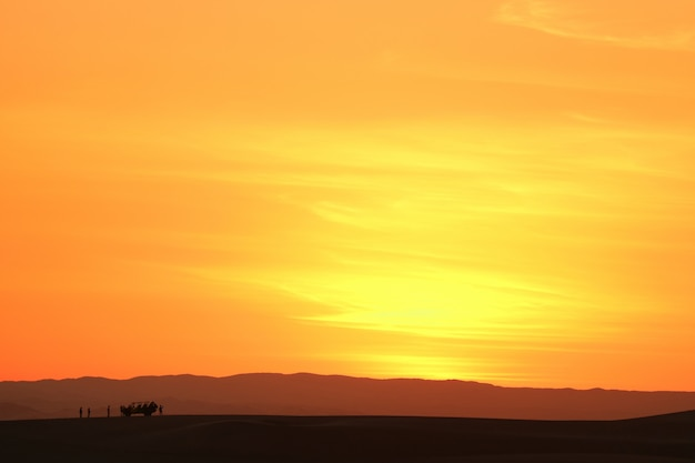 砂丘のバギーと観光客、ペルーのシルエットとhuacachina砂漠の砂丘の上の空 Premium写真