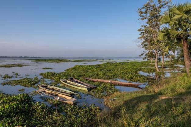 曇り空の自然な背景、スリン、タイで屋外の森の木の近くの緑の草とhuay saneng湖の水に古い浸水木製ボート Premium写真