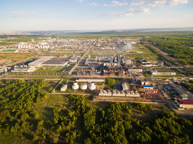 A huge oil refinery with pipes and distillation of the complex on a green field surrounded by forest Premium Photo