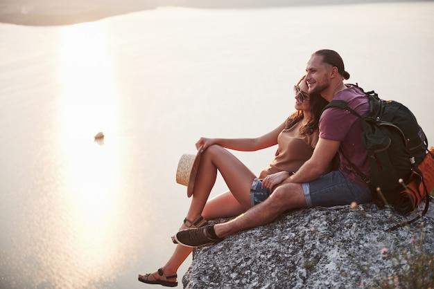 川や湖の海岸を眺めながら岩山の上に座っているバックパックとカップルを抱き締めます。 無料写真
