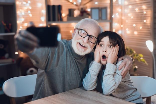 Hugging grandfather and grandson making selfie Premium Photo