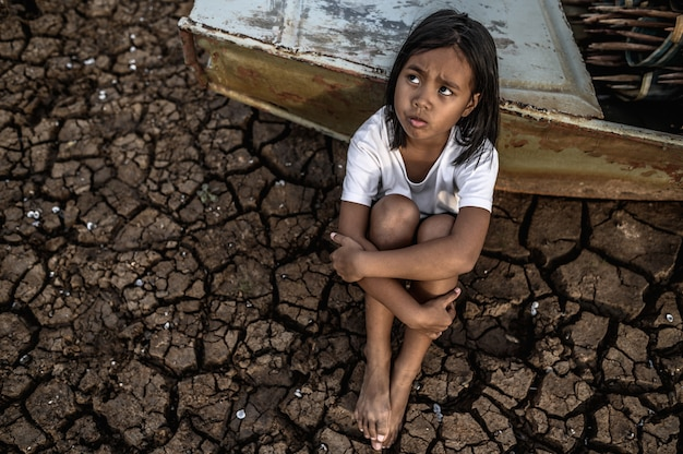 Hugging their knees and looking at the sky on dry soil and there are fishing boats, global warming. Free Photo