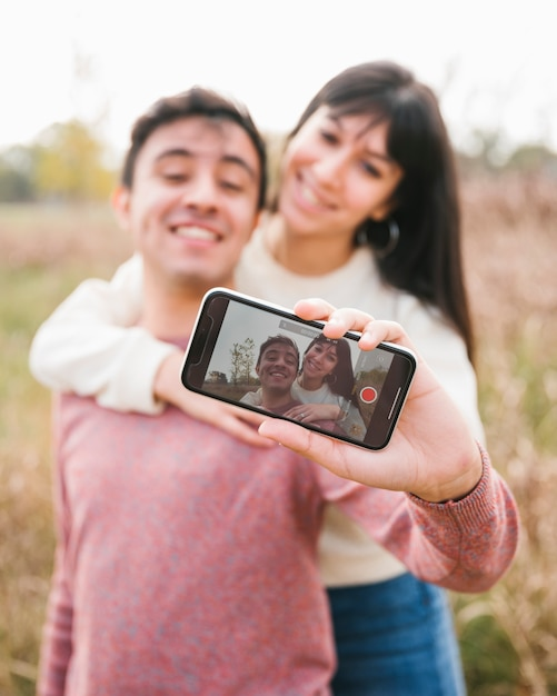 Hugging young couple taking selfie with smartphone Free Photo