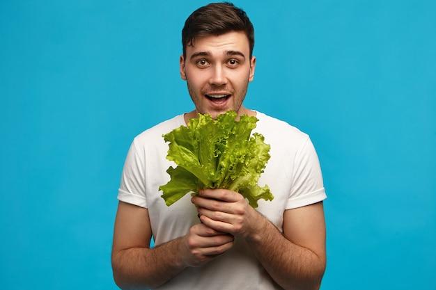 人間の感情と感情。新鮮な野菜の香りを吸い込んで、豊作に満足して、クリスピーなグリーンレタスの束を持って孤立したポーズをとっているうれしそうな若い白人の男。食品と栄養の概念 無料写真