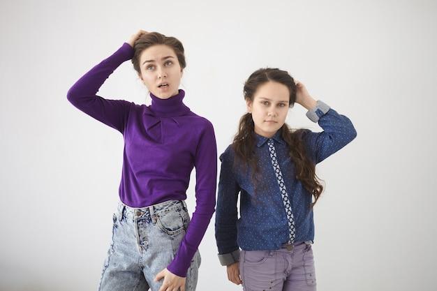 人間の感情、感情、反応、態度。白い壁に立っているスタイリッシュな服を着た2人の妹の孤立したスタジオショット 無料写真