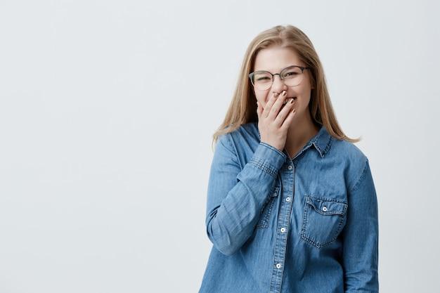 人間の顔の表情と感情。面白い冗談を真剣に笑って、カメラを見て、デニムシャツとメガネを着て、手のひらの後ろに顔を隠して若い陽気で魅力的なブロンドの女性 無料写真