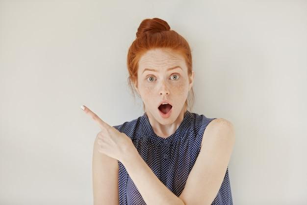 Выражения человеческого лица, эмоции и чувства. удивленная и шокированная молодая рыжая женщина в рубашке без рукавов указывает на глухую стену Бесплатные Фотографии