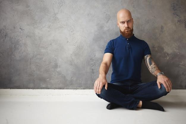 Выражения лица и язык тела человека. эмоциональный сварливый молодой небритый бородатый мужчина с бритой головой сидит на полу, скрестив ноги, злится, но не может расслабиться, пытается медитировать Бесплатные Фотографии