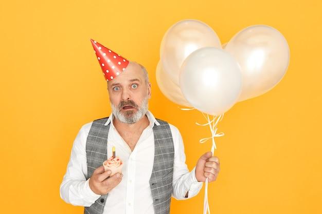 인간의 표정, 감정 및 감정. 겁에 질린 표정을 가진 생일 컵케익과 흰색 헬륨 풍선을 들고 회색 수염을 가진 정서적 충격을받은 수석 남자의 그림 무료 사진