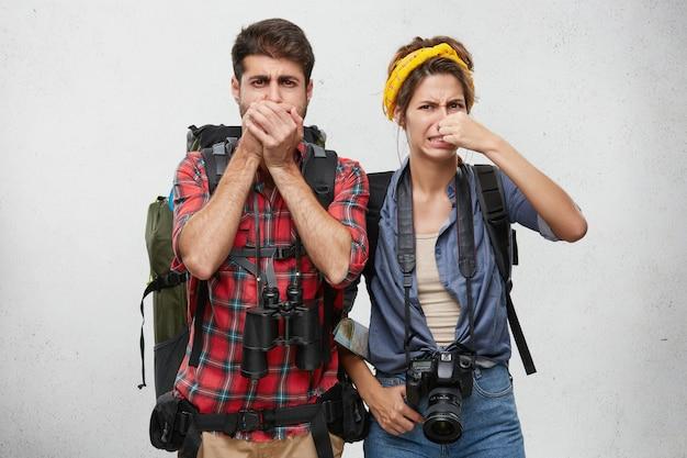 人間の表情、感情、感情。観光と旅行。悪臭を放つ悪臭のために観光用の服装でアクティブな若いカップル、バックパック、双眼鏡、写真用カメラの鼻をつまむ 無料写真