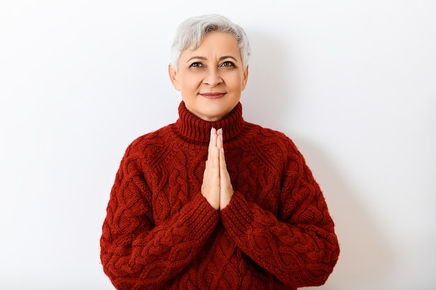 Выражения лица, эмоции, чувства и реакция человека. изолированное изображение позитивной веселой пенсионерки с короткими волосами, глядя вверх с счастливой улыбкой, взявшись за руки в молитве, с обнадеживающим взглядом Бесплатные Фотографии