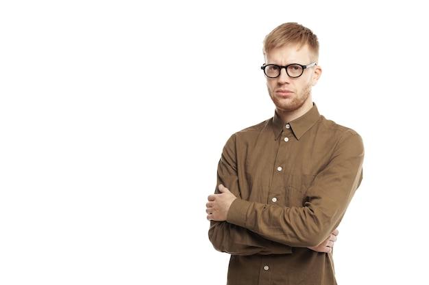 人間の表情、感情、感情、反応、態度、人生の知覚。しぶしぶ頑固な若い白人のひげを生やした男が腕を組んで真剣に見ている 無料写真