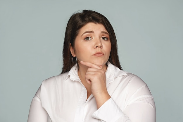 Human facial expressions, feelings and emotions. pensive thoughtful young european businesswoman with large curvy body touching her chin Free Photo