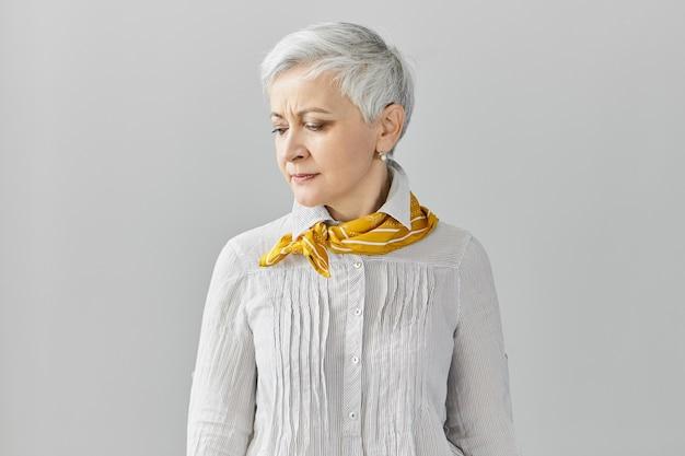 Espressioni facciali umane. accigliato dispiaciuto triste pensionato femmina con capelli grigi pixie che ha mal di testa, guardando in basso, in posa isolato al muro bianco con copyspace per il contenuto pubblicitario Foto Gratuite