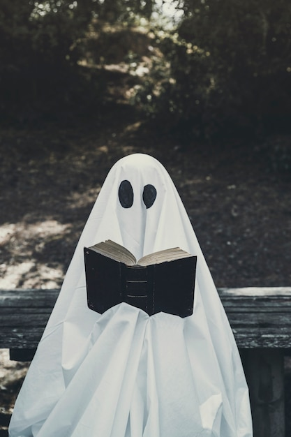 Human in ghost suit sitting on bench and reading book Free Photo
