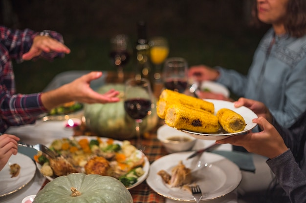 Human giving cooked corns to person at family dinner Free Photo