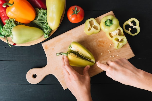 Human hand cutting green bell pepper on wooden chopping board Free Photo