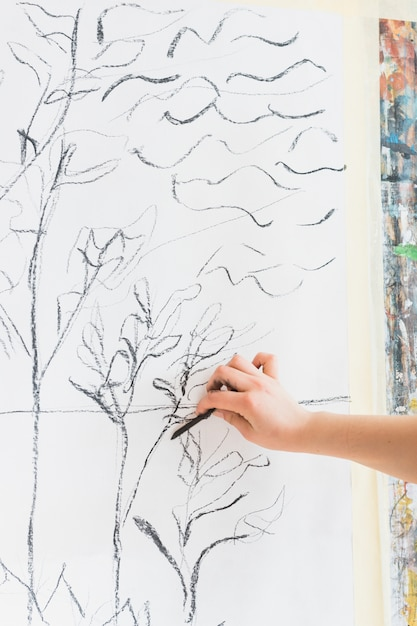Human hand drawing on canvas using charcoal stick Free Photo