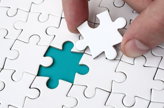 The human hand fills the last missing elements of the surface from the jigsaw puzzle. Premium Photo