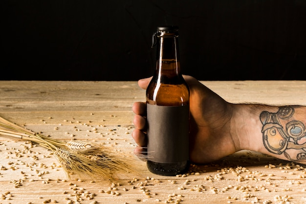Human hand holding alcoholic bottle with ears of wheat on wooden surface Free Photo