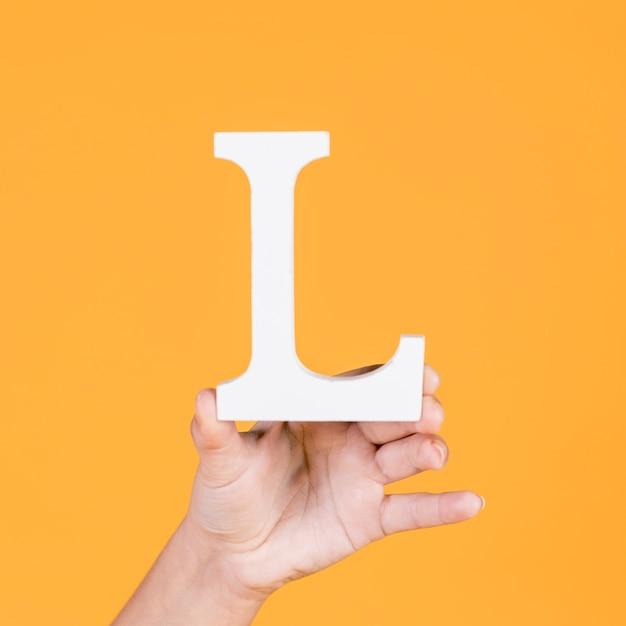 Human hand holding alphabet l Free Photo