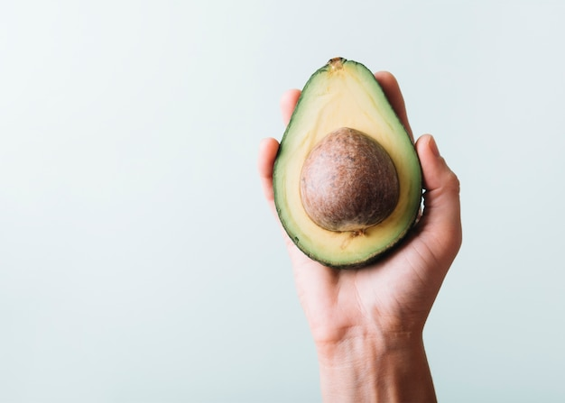 Human hand holding avocado on green background Free Photo