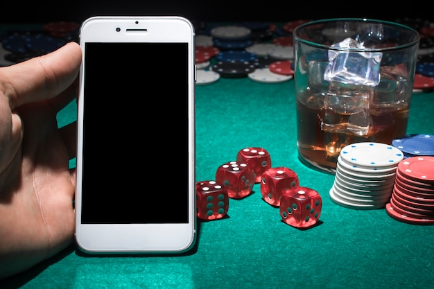 Human hand holding cellphone on casino table Free Photo