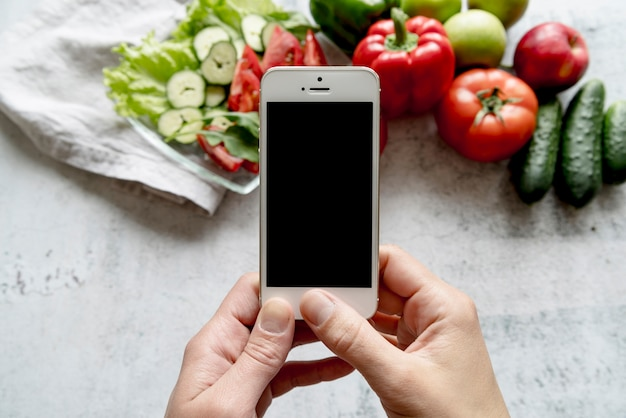 Human hand holding cellphone over organic vegetables on concrete backdrop Free Photo