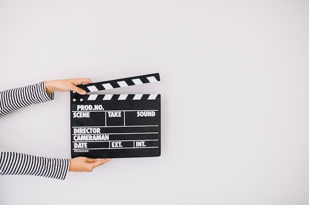 Human hand holding clapper board on white background Premium Photo