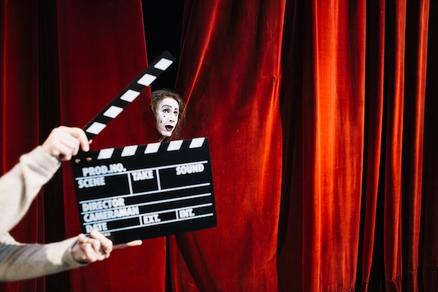 Human hand holding clapperboard in front of male mime artist face Free Photo