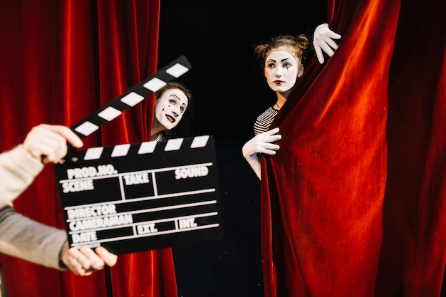 Human hand holding clapperboard in front of two mime artist performing on stage Free Photo