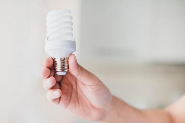 Human hand holding compact fluorescent light bulb