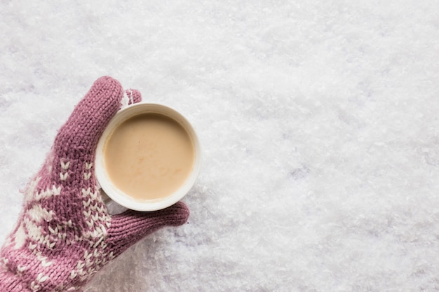 Human hand holding cup of coffee over the snowy land Free Photo