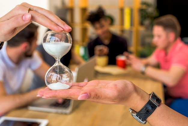 Human hand holding hourglass in front of people at background Free Photo