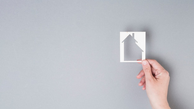 Human hand holding house cutout on grey background Free Photo