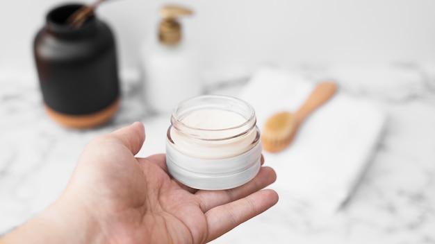 Human hand holding jar of moisturizing cream Free Photo