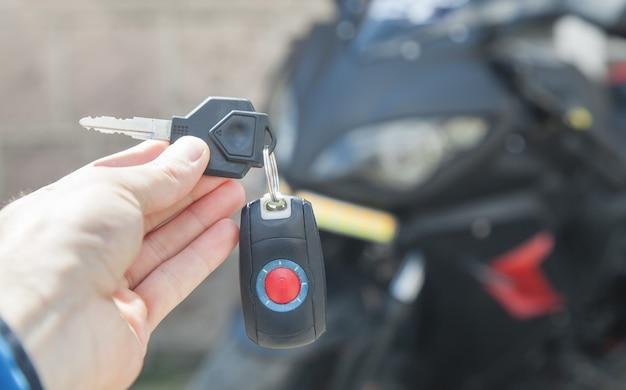 オートバイのライフスタイルの背景にキーを保持している人間の手 Premium写真