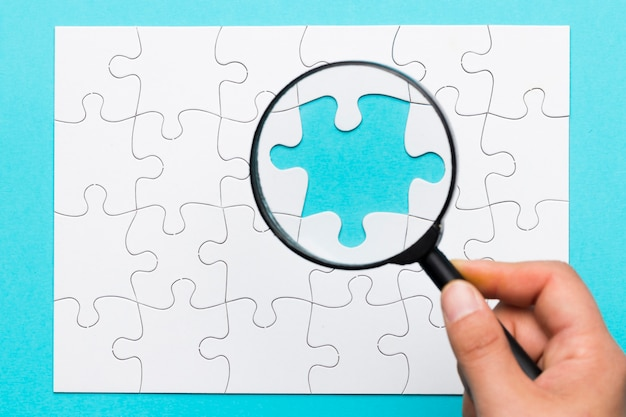Human hand holding magnifying glass over missing puzzle piece Free Photo