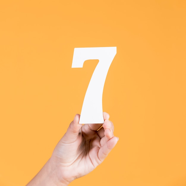Human hand holding number seven against yellow background Free Photo