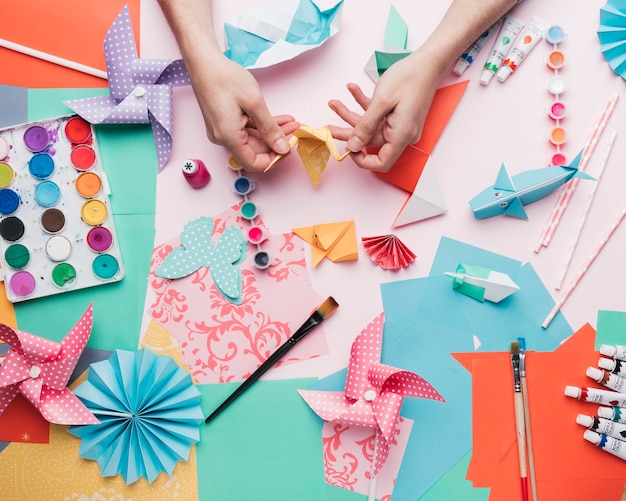 Human hand holding origami bird over craft product Free Photo