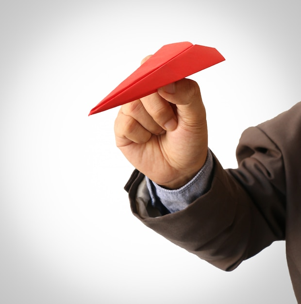 Human hand holding red paper airplane Premium Photo