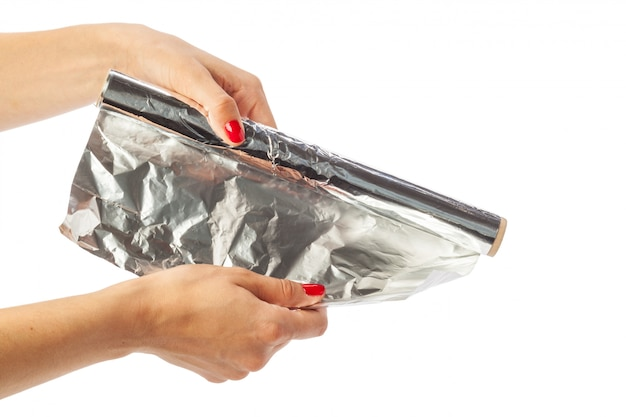 Human hand holding a roll of foil isolated on white Premium Photo